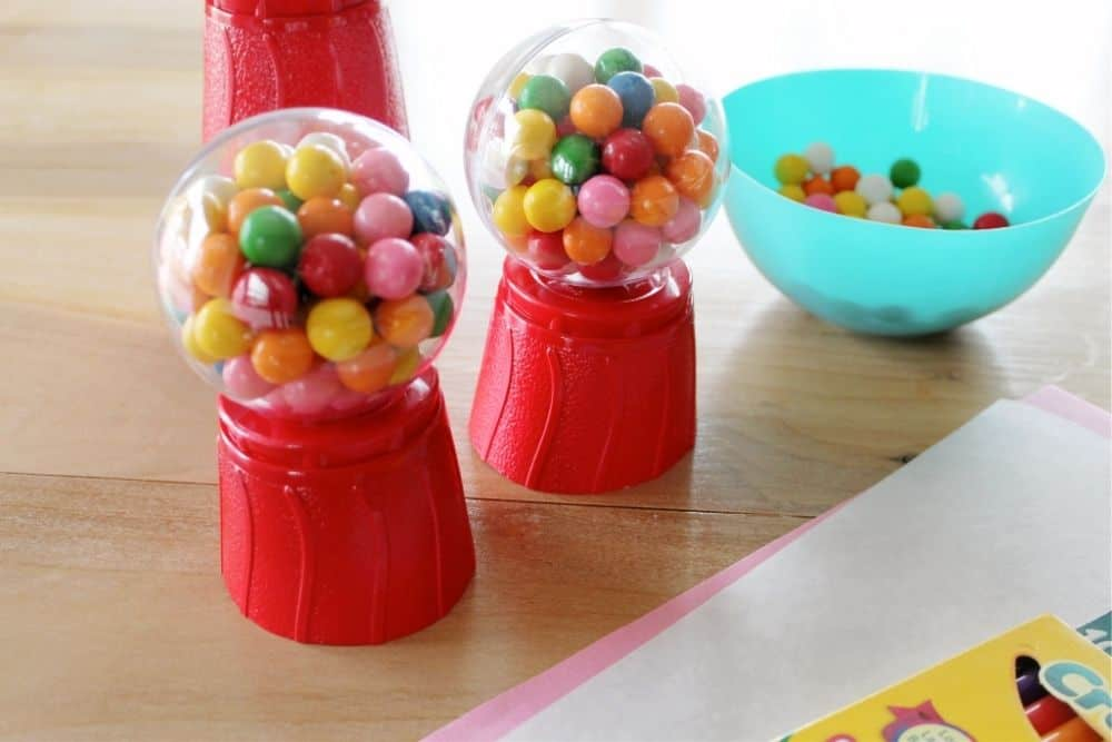 Two almost finished DIY gumball machines sitting on a table.