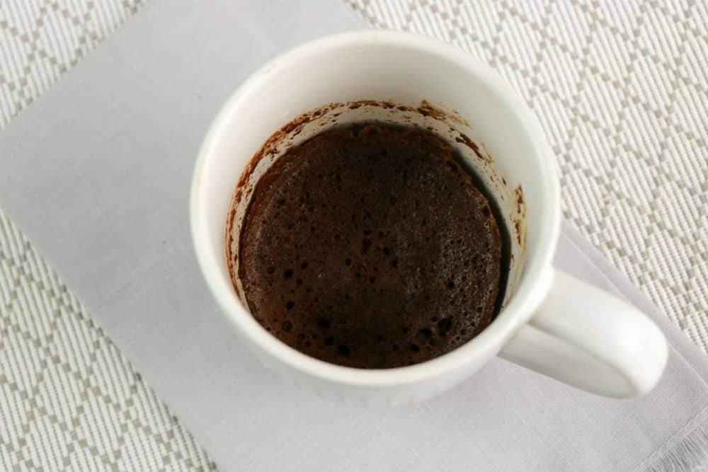 Cooked Chocolate Keto Mug Cake sitting on a gray napkin.