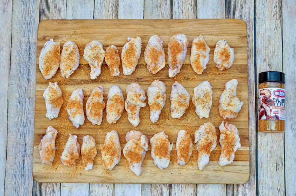A bunch of raw chicken wings covered in Cajun seasoning blend on a wooden cutting board.