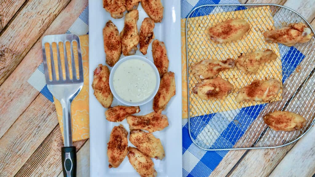 Air Fried chicken wings seasoned with Cajun seasoning blend, sitting on a plate with a bowl of ranch dressing.