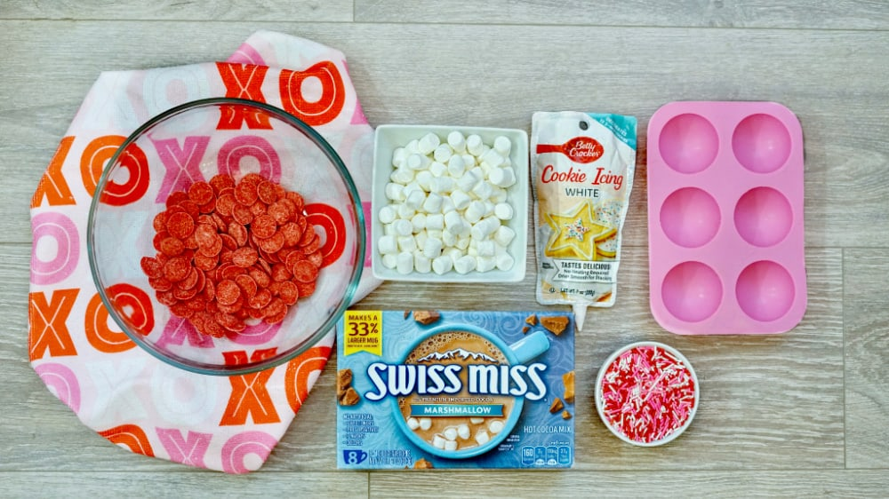 Ingredients to make Valentine's Day hot chocolate balls, including red candy melts, mini marshmallows, white icing, silicone mold, Swiss Miss hot chocolate and Valentine's Day sprinkles.