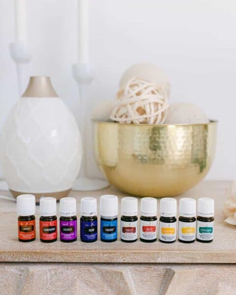 A display of Young Living essential oils lined up on a table.