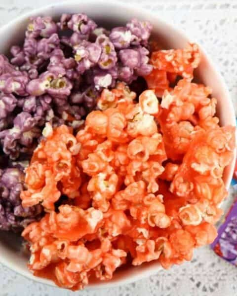 A cowl filled with purple and orange colored popcorn sitting next to several packets of Kool Aid drink mix.
