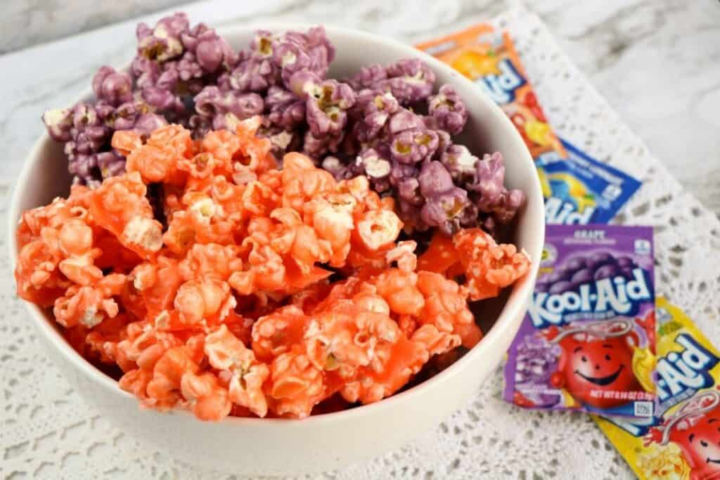 Orange and purple colored popcorn in a white bowl, sitting on a table next to packets of drink mix.