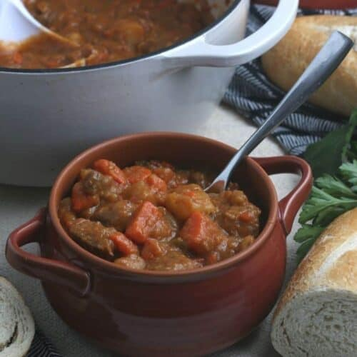 A bowl full of beef stew sitting on a table with bread.