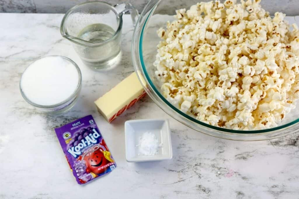 The ingredients for making flavored popcorn aitting on a table, including Kool-Aid drink mix, butter, corn syrup, baking, sugar and baking powder.