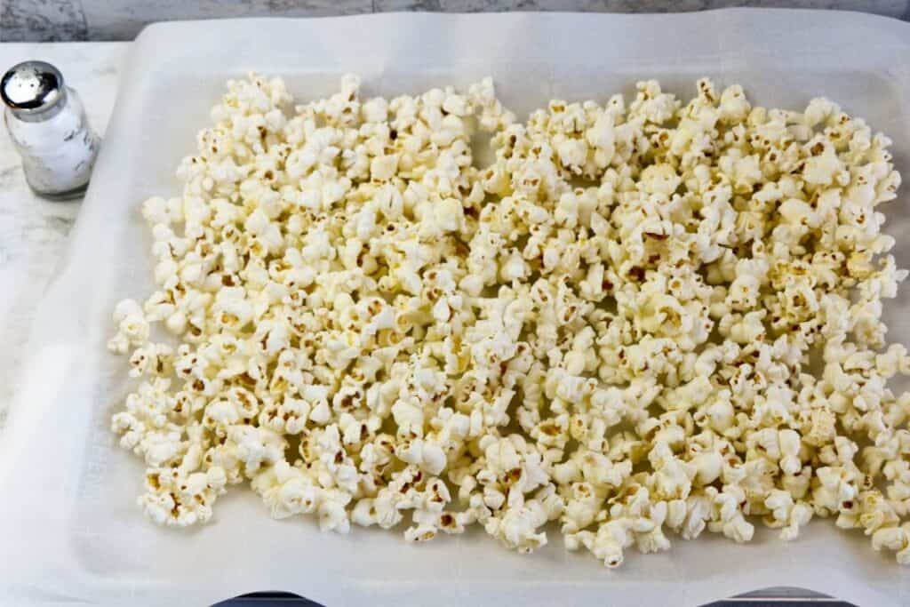 popped popcorn on a lined cookie sheet.