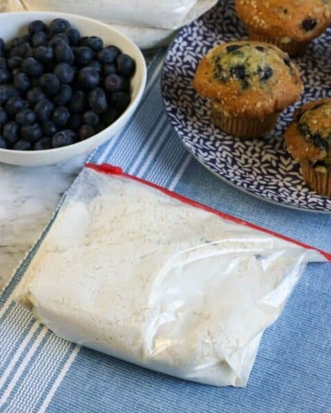 muffin mix in a ziplock bag sitting on a table with a bowl of blueberries and a plateful of blueberry muffins.
