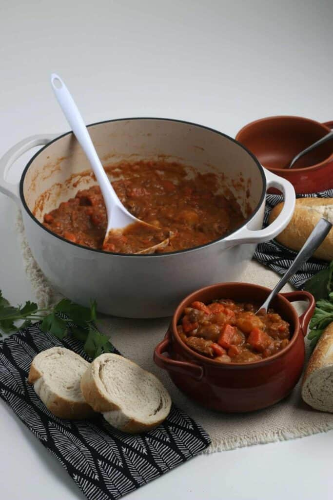 A pot of beef stew sitting near a bowl of stew with homemade bread nearby.