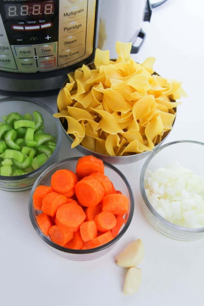 Chicken noodle soup ingredients sitting in individual bowls in front of an Instant Pot. Ingredients include egg noodles, garlic cloves, diced celery and carrots and chopped onions.