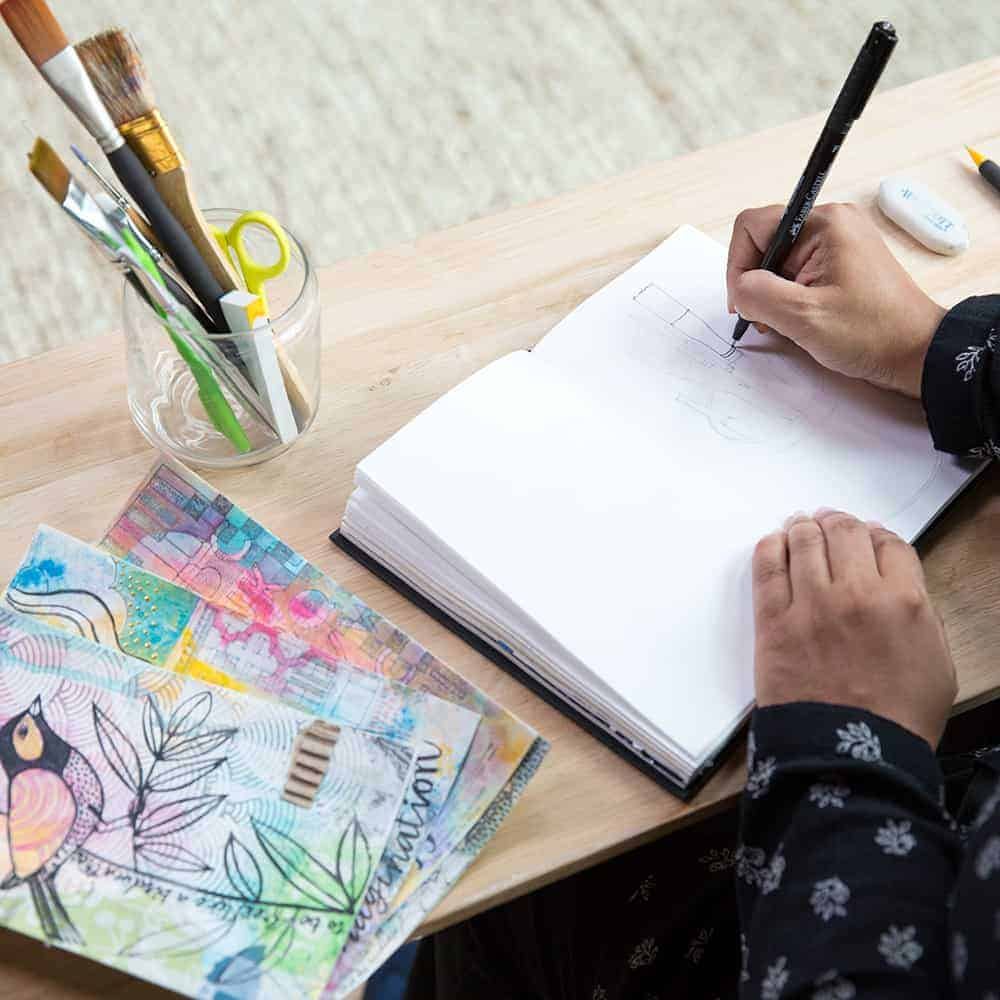 Woman doodling in notebook with paints, pens, and water colors on her desk.