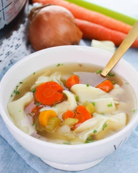 a bowl of chicken noodle soup with an onion and carrots sitting on a table beside it.