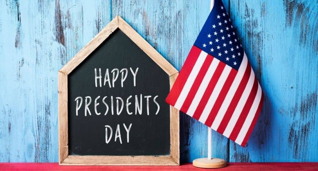 chalkboard sign that says Happy President's Day, sitting next to an American Flag on a table.