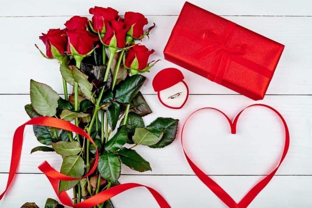 red roses sitting a table with a ring in a box and a wrapped gift for Valentine's Day.