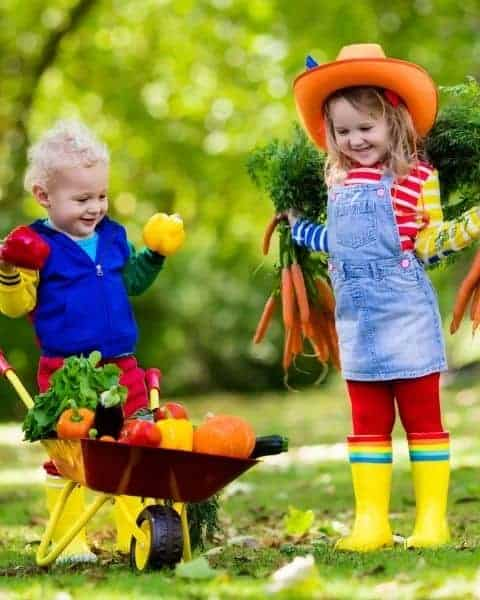 Two small children in boots and hats in the garden.