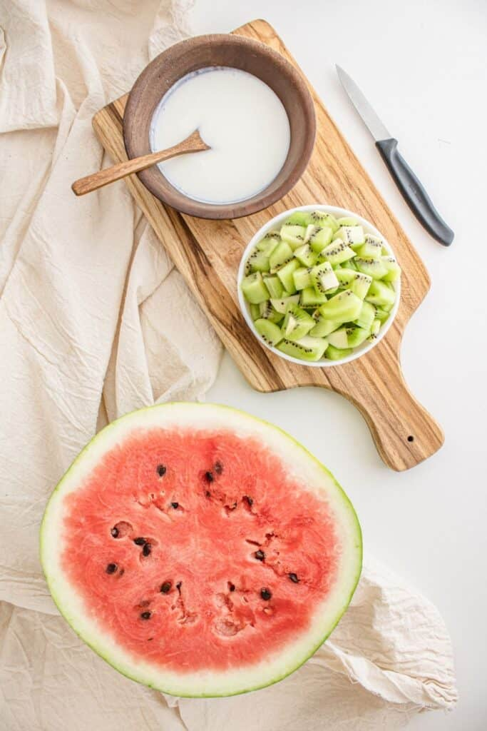 Bowl of cream, sliced kiwi, and watermelon.