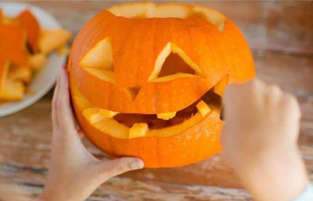 A woman carving a pumpkin's mouth.
